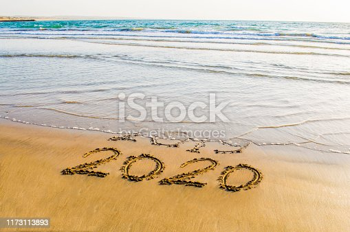 istock Happy New Year 2020 text on the sea beach. Abstract background photo of coming New Year 2020 and leaving year of 2019 1173113893