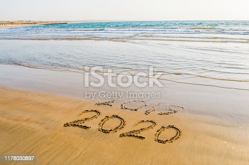 istock Happy New Year 2020 text on the sea beach. Abstract background photo of coming New Year 2020 and leaving year of 2019 1178030897
