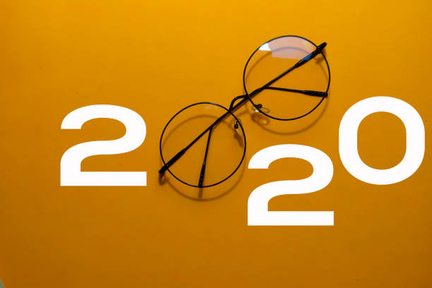 Happy New Year 2020 with Glasses isolated on yellow background stock photo