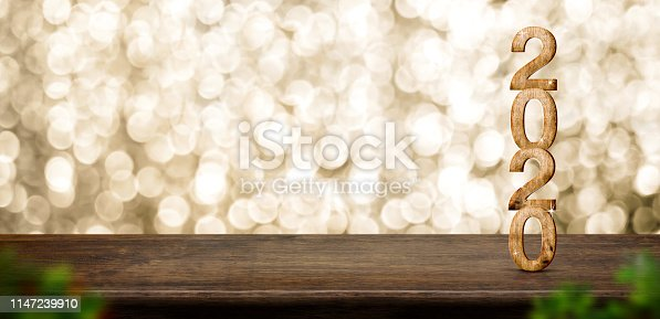 istock Happy New Year 2020 wood with sparkling star on brown wood table with gold bokeh background,Holiday festive celebration concept.Banner mock up for display of product or design content 1147239910