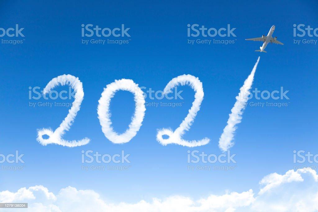 счастливый Новый год 2021 концепции. облако рисунок самолетом в небе - Стоковые фото 2021 роялти-фри