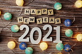 Happy New Year 2021 decorate with LED coton ball on wooden background