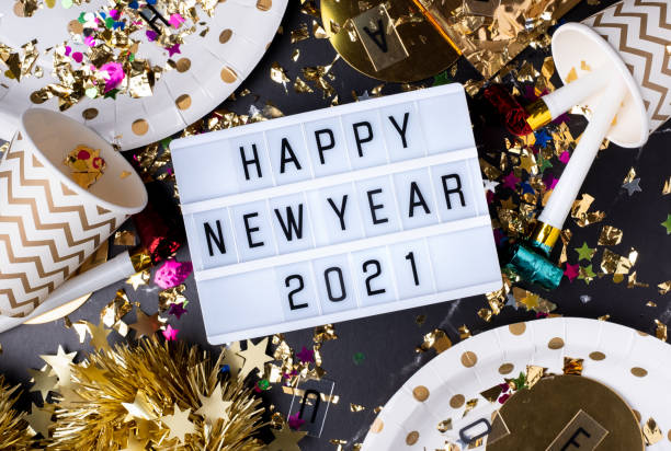 Happy new year 2021 on light box with party cup,party blower,tinsel,confetti.Fun Celebrate holiday party time table top view stock photo