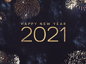 istock Happy New Year 2021 Text Holiday Graphic with Gold Fireworks Background in Night Sky 1270874641