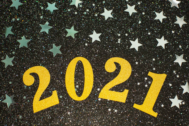 Happy New year 2021 with silwer glitter stars on black background. stock photo