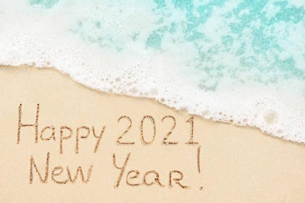 Happy New Year 2021 written on sandy beach stock photo