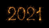 istock Happy New Year 2021 written with bengal fire, sparkler fireworks candle isolated on a black background. New Year dark background. 1202988480