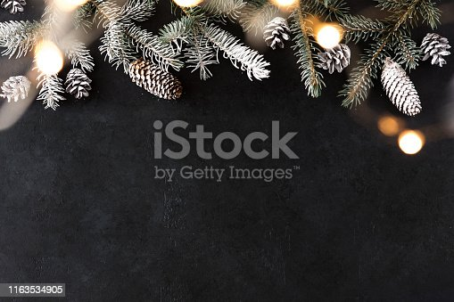 Happy New Year and Merry Christmas with sparkling garland on black stone table with gold bokeh background and pine branches. Holiday festive concept.