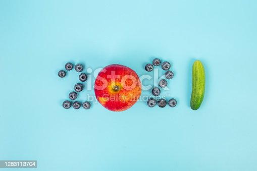 2021 Happy New Year and New You with fruits and Vegetables; Blueberries, Red apple and cucumber on blue background. Goals, Healthy, Resolution, Time to New Start and dieting concept