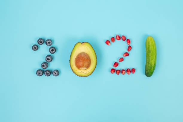 2021 happy new year en new you met fruit; bosbessen, avocado, granaatappelzaden en komkommer op blauwe achtergrond. doelen, gezond, resolutie, time to new start en dieetconcept - fresh start yellow stockfoto's en -beelden
