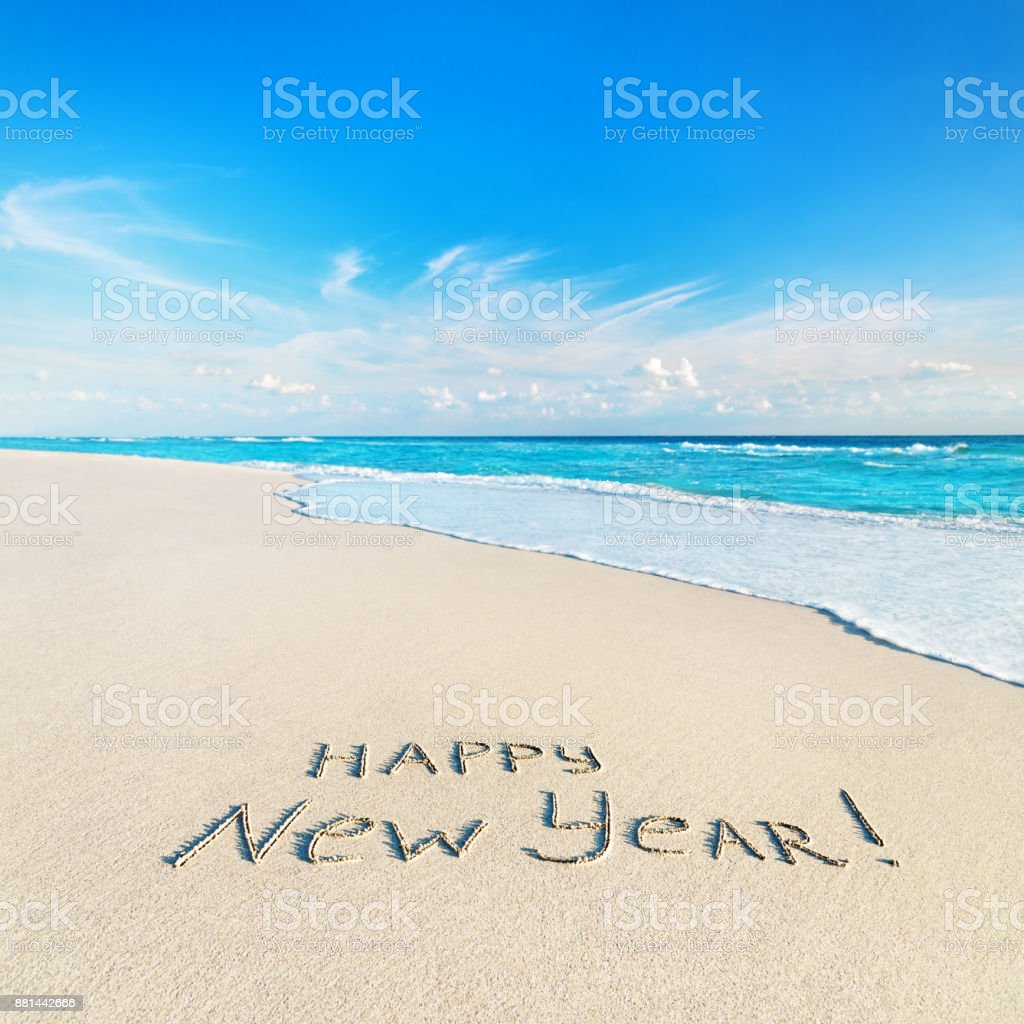 Happy New Year caption at tropical ocean beach against waves stock photo