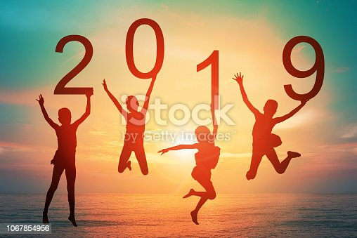 istock Happy new year card 2019 retro or lomo style. Silhouette of children girl  jumping on tropical beach with vintage sunset sky background. Kids holding the number 2019 with sea and sunrise background. 1067854956