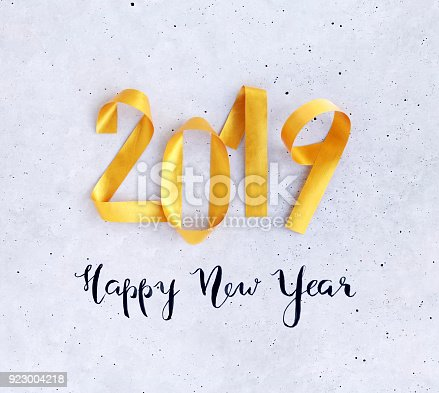 istock Happy New Year card 2019 with golden numbers on concrete background 923004218