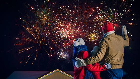 Happy New Year Celebration, Young Family of Three Standing in the Front Yard Watching Beautiful Fireworks. In the Evening while Snow is Falling Father, Mother and Cute Little Daughter Look up in Wonder. House Decorated with Garlands for Christmas Eve.