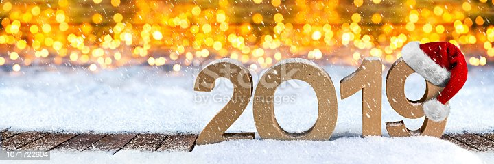 1080262636 istock photo 2019 happy new year christmas greeting card number symbol lettering wooden lights bokeh panorama snow background 1071722604