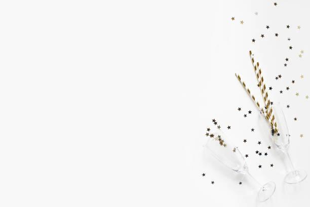 happy new year zusammensetzung. sektgläser mit goldenen konfetti sterne und trinkhalme auf weißen tisch hintergrund isoliert. feier, party konzept. flach legen, top aussicht. leere kopie raum. - schaumwein fotos stock-fotos und bilder