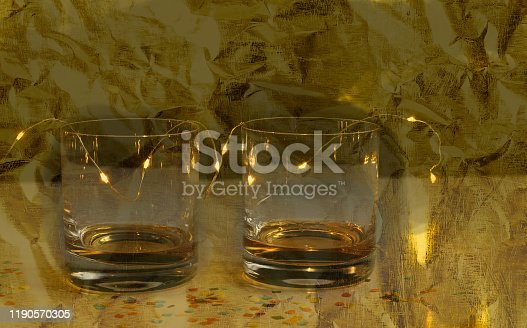 1144550840 istock photo Happy New Year composition. Two glasses and confetti isolated on gold background.New year 2020.Celebration Greeting Concept. 1190570305