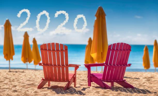 2020 Frohes Neujahrskonzept und zwei Liegestühle am Strand – Foto