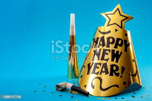 Happy new year concept with a festive hat, noisemakers, confetti, party blower  and paper trumpet isolated on blue background with copy space