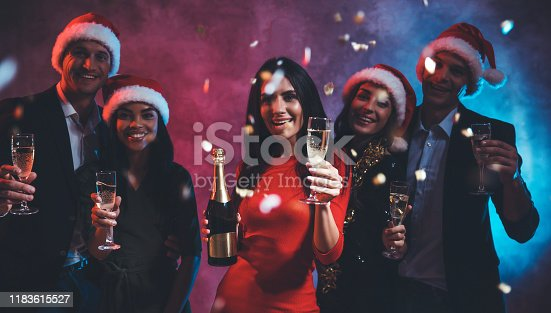 497317250 istock photo Happy New Year! Five good-looking people are posing together in Santa hats, with glasses of champagne in their hands, smiling and looking at the camera, having a confetti all around them. 1183615527
