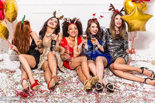 Group of beautiful young girls celebrating New Year. Sitting on floor, cheering with champagne. Wear elegant dresses. Confetti are all over the room. Room is decorated with star and heart  shaped balloons.