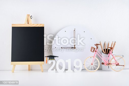 istock 2019 happy new year / graduate study abroad program, time schedule arrangement, education concept : Black graduation cap of success on number 2019 white wood cut, clock on student desk, office table 1057856978