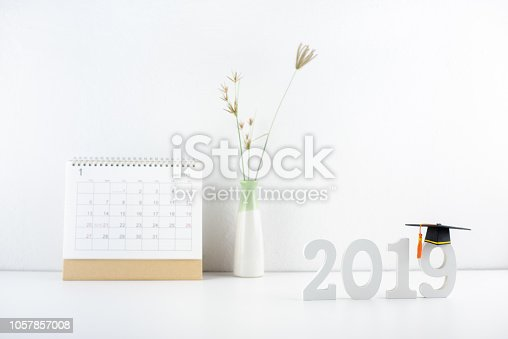 istock 2019 happy new year / graduate study abroad program, time schedule arrangement, education concept : Black graduation cap of success on number 2019 white wood cut on student desk, pupil studying table 1057857008