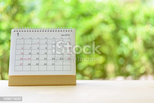 istock 2019 happy new year, green nature theme concept : Desktop flipped / spiral paper calendar on a table in a public garden, depicts freshness and happiness in new year and upcoming life, bokeh background 1058275032