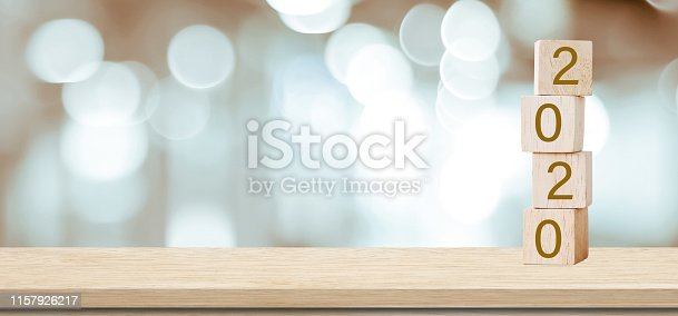 istock 2020 happy new year greeting card, Wooden cubes with 2020 over blur bokeh background with copy space for text, Happy new year banner 1157926217
