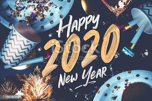 2020 happy new year hand brush storke font on marble table with party cup,party blower,tinsel,confetti.Fun Celebrate holiday party time table top view.blue modern tone filter.festive greeting card
