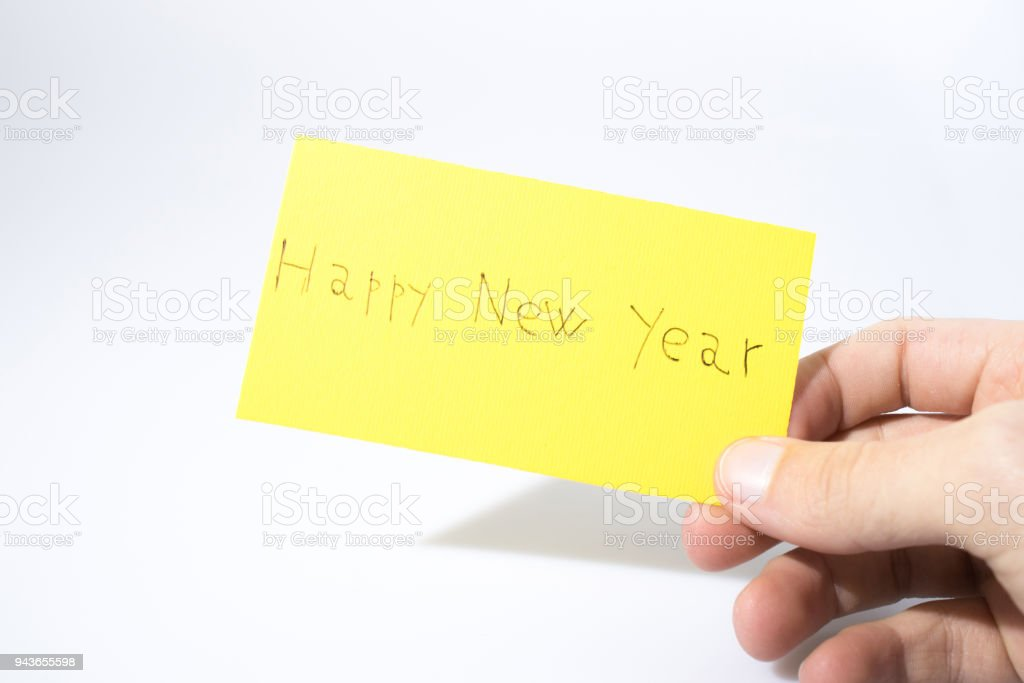 Happy new year handwrite with a hand on a yellow paper composition stock photo
