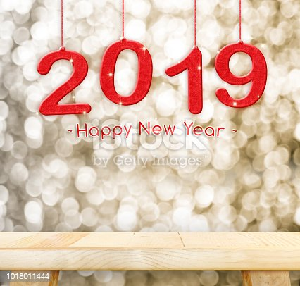 istock 2019 Happy new year hanging over plain wood table top with blur gold sparkling bokeh light,Holiday concept,leave space for adding your design. 1018011444