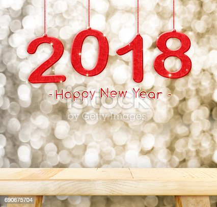 istock 2018 Happy new year hanging over plain wood table top with blur gold sparkling bokeh light,Holiday concept,leave space for adding your design 690675704
