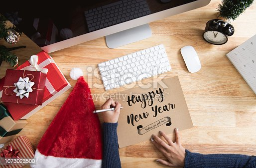 1073023470 istock photo Happy new year holiday greeting paper card design mockup with decoration on wood table. 1073023500