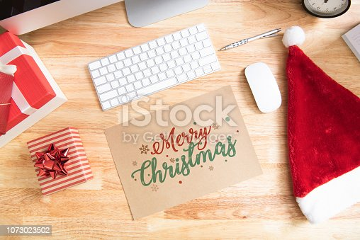 1073023470istockphoto Happy new year holiday greeting paper card design mockup with decoration on wood table. 1073023502