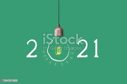 2021 Happy New Year. Light bulb on a green background. Festive background.
