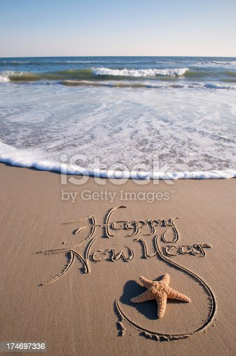Happy New Year scrawled in fancy script on the beach is accented by a nice starfish