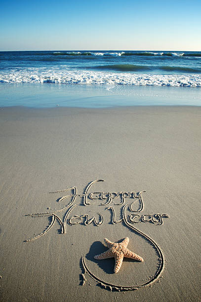 Happy New Year Message w Starfish on Smooth Beach stock photo