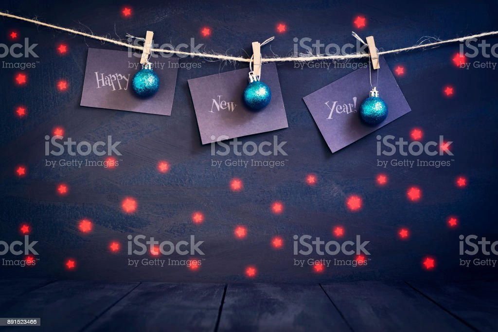 Happy new year on paper with a clothespin, hanging on a rope on a...