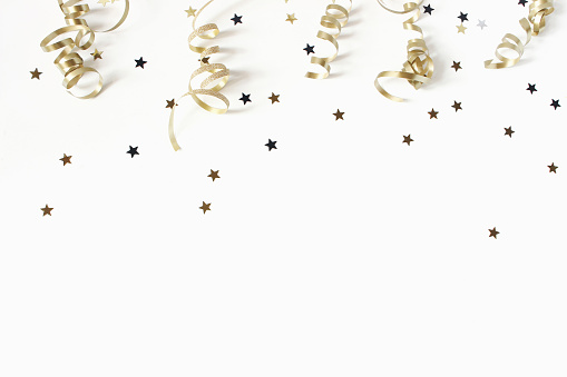 Happy New Year or birthday festive composition. Golden confetti and glittering stars on white table background. Celebration, party concept. Flat lay, top view, empty copy space.