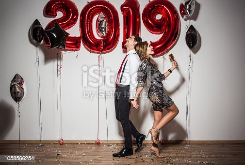 Young couple celebrating New Year party. Holding baloons and enjoying in evening.
