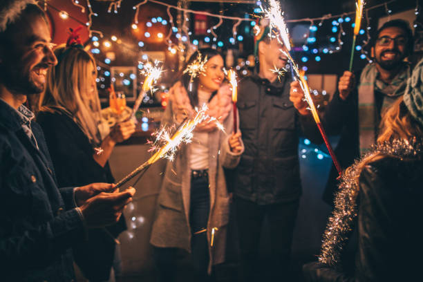 Happy New Year!!! Photo of a cheerful group of friends, at an outdoor New Year's celebration, lightning sparklers at midnight new year's eve stock pictures, royalty-free photos & images