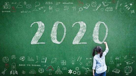 istock 2020 Happy new year school class academic calendar with student kid's hand drawing greeting on teacher's green chalkboard for educational celebration, back to school, STEM education classroom schedule 1183657067