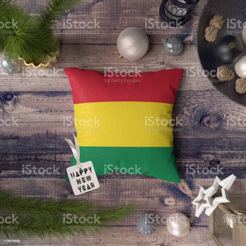 Happy New Year tag with Bolivia flag on pillow. Christmas decoration concept on wooden table with lovely objects. stock photo