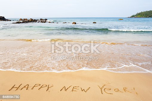 istock Happy New Year text on the sea beach. 648594730