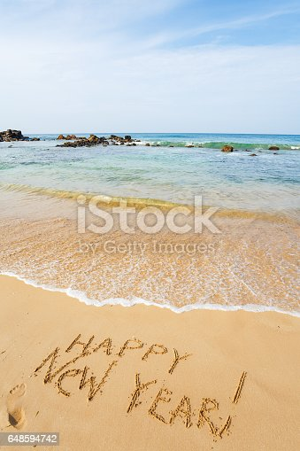 istock Happy New Year text on the sea beach. 648594742