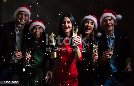 497317250 istock photo Happy New Year! Three gorgeous girls in amazing outfits and two handsome men are celebrating New Year's Eve drinking champagne, smiling and throwing confetti up in the air. 1183612060