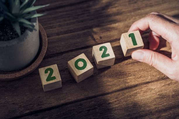 2021 happy new year with hand pick up wood block on wood table with sunlight from window.hope for new year concept stock photo