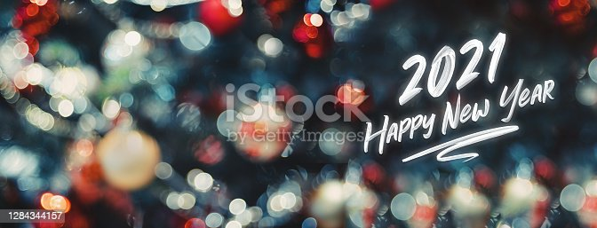 2021 happy new year word on abstract bokeh of  ball and string lights on xmas tree.holiday celebration greeting card