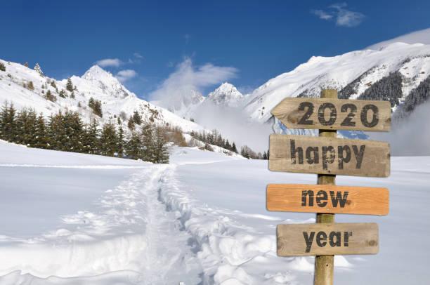 2020 feliz año nuevo escrito en un post-sign en la nieve sobre fondo de montaña blanco - foto de stock